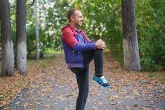 Bawi się mężczyzna rozciąganie przy parkową jesienią, robi ćwiczeniom Sprawności fizycznych pojęcia Zdjęcia Royalty Free