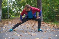 Bawi się mężczyzna rozciąganie przy parkową jesienią, robi ćwiczeniom Sprawności fizycznych pojęcia Zdjęcia Stock