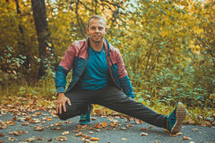 Bawi się mężczyzna rozciąganie przy parkową jesienią, robi Zdjęcia Royalty Free