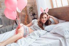 Bawi się, młoda kobieta jest ubranym królików ucho na łóżku z balonami w domu obrazy royalty free