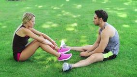 Bawi się pary odpoczywa na trawie po plenerowego treningu mężczyzna kobiety potomstwa zbiory