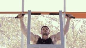 Bawi się styl życia, mięśniowy sportowiec z pięknymi sportowymi ciał ciągnieniami na w górę symulanta podczas władza treningu prz zbiory