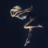 Bawi się, szczupła młoda dziewczyna z mięśniowym ciałem robi skokowi na bla Zdjęcie Stock