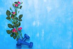 Bawi się tło z błękitnymi dumbbells i kwitnie Fotografia Royalty Free