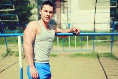 Bawi się, uliczny treningu pojęcie - uśmiechnięty sportowiec blisko horyzontalnego baru Zdjęcie Stock