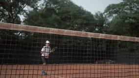 Bawi się zwycięstwo, szczęśliwy ambitny gracza w tenisa nastolatek chłopiec z kantem raduje się wygranego mistrzostwo tenisa przy zbiory