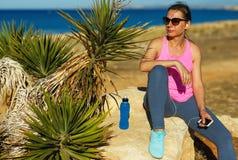 Bawi się dziewczyny odpoczywa po jogging na skale morzem Zdjęcie Stock