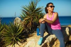 Bawi się dziewczyny odpoczywa po jogging na skale morzem Obrazy Royalty Free