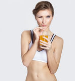 Bawjący się pięknej młodej uśmiechniętej dziewczyny z szkłem sok pomarańczowy w jego rękach mruga, zdrowy utrzymanie, fotografii  Obrazy Royalty Free