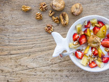 A bawl of fruit, walnuts and yogurt. A cup of Turkish coffee with sweets and spices on a rough wooden surface royalty free stock photo