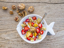 A bawl of fruit, walnuts and yogurt. On a rought wooden surface stock photography