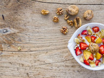 A bawl of fruit, walnuts and yogurt. On a rought wooden surface stock photos