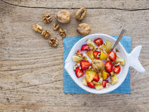 A bawl of fruit, walnuts and yogurt. On a rought wooden surface stock photo