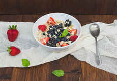 A bawl of oat porridge with fresh berries, honey, almond petals Royalty Free Stock Photography