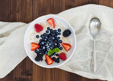 A bawl of oat porridge with fresh berries, honey, almond petals Royalty Free Stock Image