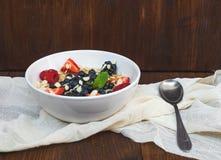 A bawl of oat porridge with fresh berries, honey, almond petals Royalty Free Stock Photos