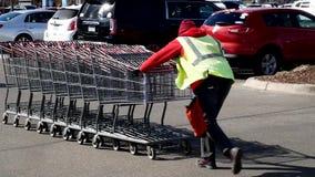BAXTER, MANGAN - 29. MÄRZ 2019: Costco-Einkaufswagenbegleiter drückt Wagen zurück zu Speicher von der Parkplatzhürde stock footage