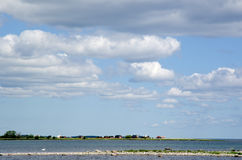 Bay. Calm bay with coastline of small houses an a sky with white clouda Stock Photography