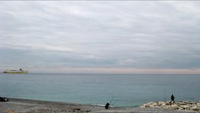 Bay of Angels in Nice on a cloudy winter morning. Timelapse of people fishing and resting at the Bay of Angels, Nice, France, and of a ferry calling at the port stock footage