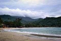 A bay with beaches and dark rain clouds over the jungle Stock Photo