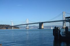 Bay Bridge over the bay in San Francisco, California. The Bay Bridge, a California landmark, over the San Francisco Bay on a sunny day with blue skies Royalty Free Stock Photos