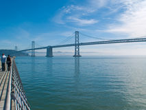 The Bay Bridge in San Francisco. A wide-angle view of the famous Bay Bridge in San Francisco, California. People/tourists can be seen strolling on the pier to Stock Photo