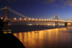 Bay Bridge, San Francisco glows in the dusk. With traffic taillights leaving red ribbons across its' span Royalty Free Stock Photography