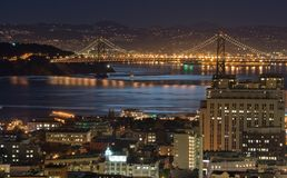 Bay Bridge, San Francisco under moonlight. Full moon is reflected from the Bay. The North Beach district is in the foreground in this zoom shot of Bay Bridge Stock Images