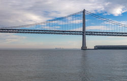Bay Bridge, San Fransisco, America with cloudy sky and calm watr Royalty Free Stock Photography