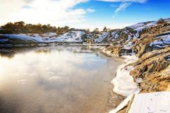 Bay with dock surrounded by rocky coast in winter Royalty Free Stock Photo