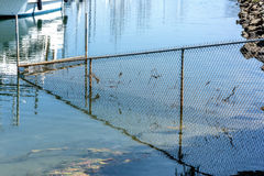 Bay fence. Bay wire mesh fence partly drowned in water and its reflection Stock Image