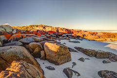Bay of Fires. Scenic and pristine white sandy beach with turquoise crystal waters and orange lichen covered granite boulders at sunset. The Gardens in the Bay of Royalty Free Stock Image