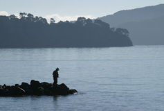 Bay Fishing. Silhouette of man fishing off jetty in bay Stock Photos