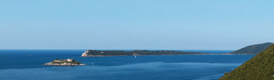 Bay Gertsegnovska in Adriatic Sea. Island Mamula or Lastavica with Fort. Calm sea and clear blue sky. Panorama Stock Image