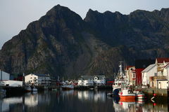Bay of henningsvear in norway. Bay and port of henningsvear in norway with the mounatins overhanging. Colored port of the lofoten islands Stock Images
