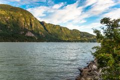 Impressive Forested Coast Mountains at Sunset. Bay with Impressive Forested Mountains in Background at Sunset. Howe Sound, Squamish, BC, Canada stock photography