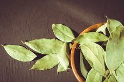 bay leaf on a dark surface/bay leaf in a wooden bowl on a black stone background. Top view royalty free stock photo