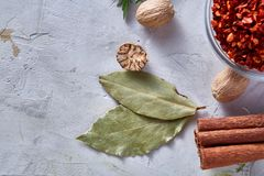 Bay leaf, nutmeg and cinnamon on white textured background, top view, close-up, selective focus. Scented condiment. Aromatic spices. Exotic ingredient. Indian Royalty Free Stock Photography