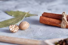 Bay leaf, nutmeg and cinnamon on white textured background, top view, close-up, selective focus. Scented condiment. Aromatic spices. Exotic ingredient. Indian Stock Photo