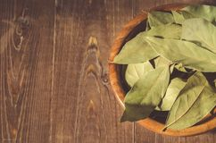 Bay leaf in a wooden bowl/bay leaf in a wooden bowl on a wooden stock photos