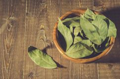 Bay leaf in a wooden bowl/bay leaf on a wooden surface. Top view stock images