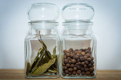 Bay leaves and allspice in a glass jar. On the wooden shelf stock images