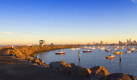 Bay at morning. Shot of the bay at sunrise with yachts and peer in foreground and city skyline in background Royalty Free Stock Photos