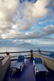 The Bay of Naples. View of a dramatic cloudscape and Mount Vesuvius over the Bay of Naples. Sun Loungers and balcony frame the scene stock image