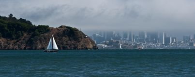 In the Bay. Sailboat glides past Angel Island with San Francisco in the background stock photos