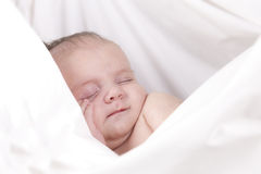 Baby sleeping. In white sheet with hand over face Royalty Free Stock Image