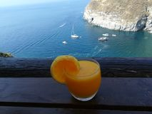 Orange juice in front of the Bay of sorgeto. Bay of sorgeto royalty free stock photos
