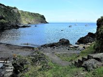 Bay with a volcanic beach, Flores island, The Azores. Steps leading down to a bay with a black volcanic beach and sailing boats, Flores island, The Azores royalty free stock photos