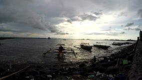 Fishing boat anchored on sea shore at twilight dusk sunset. silhouettes. Bay walk, Manila, Philippines - July 9, 2017: Fishing boats anchored on sea shore at stock video footage
