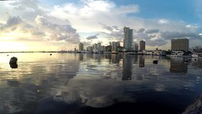 Tall buildings along sea side road viewed from opposite shore. Bay-walk, Manila, Philippines - July 9, 2017: Water reflection of Tall buildings along sea side stock footage
